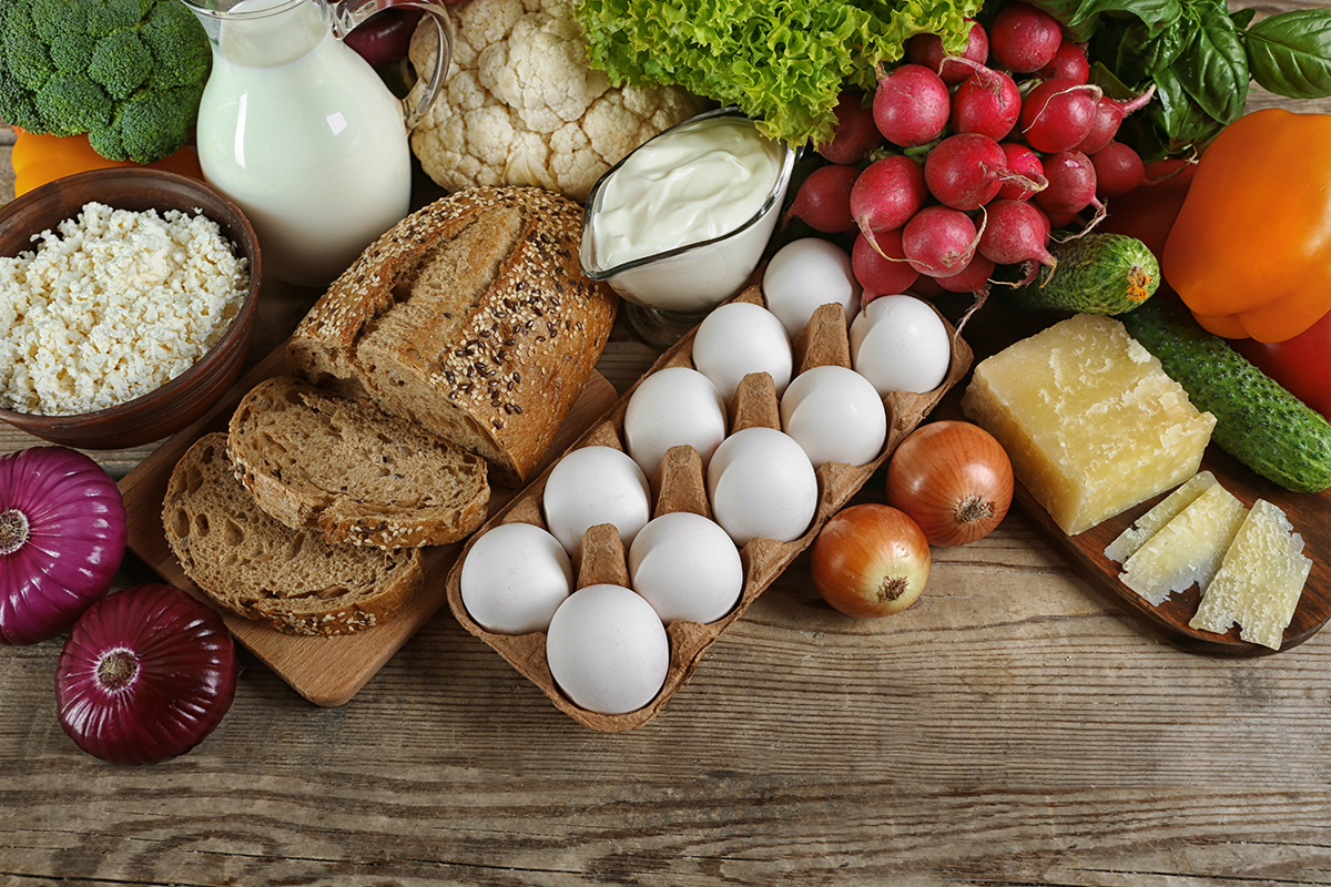 Vegetables and dairy products on wooden background